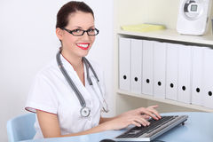 Female doctor working on pc computer. Happy female doctor in office working on pc computer Stock Images