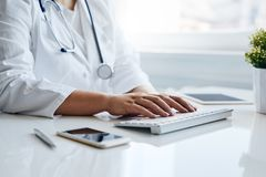 Female doctor works with computer stock images