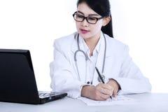 Female doctor writes medical reports. Isolated on white background Royalty Free Stock Photos