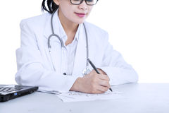 Female doctor writes notes Royalty Free Stock Image