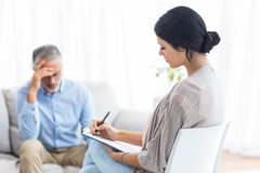 Female doctor writing on clipboard while consulting a man. Female doctor writing on clipboard while consulting a men at home Royalty Free Stock Photography