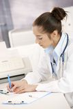 Female doctor writing at desk Stock Images