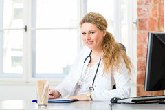 Female doctor writing document on desk in clinic Royalty Free Stock Photo