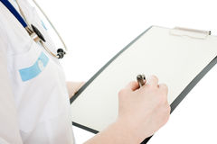 Female doctor writing on the document plate Royalty Free Stock Photography