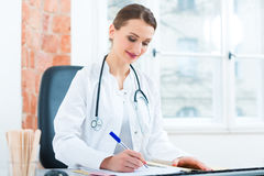 Female doctor writing in document Royalty Free Stock Images