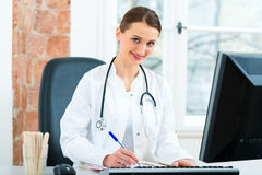 Female doctor writing in document Royalty Free Stock Photos