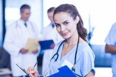 Female doctor writing a medical report. And colleagues standing behind Royalty Free Stock Image