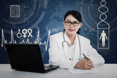 Female doctor writing a note Royalty Free Stock Image