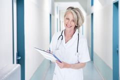 Female doctor writing notes in hospital corridor Stock Photo