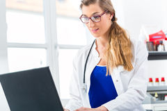 Female doctor writing on Pc in her clinic Stock Images