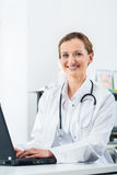 Female doctor writing on Pc in her clinic Stock Image