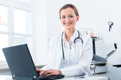 Female doctor writing on Pc in her clinic Stock Photos