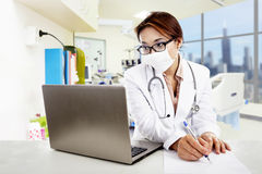 Female doctor writing prescription at hospital. Female doctor is writing a prescription while looking at her laptop in the hospital Royalty Free Stock Images