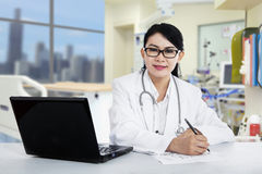 Female doctor writing prescription. Female doctor with laptop pc writing prescription in the hospital Royalty Free Stock Images