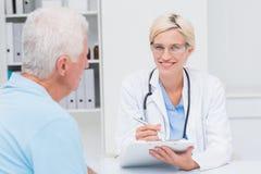 Female doctor writing prescription for senior man Stock Photos