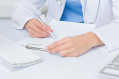 Female doctor writing prescriptions at table Royalty Free Stock Images