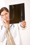 Female doctor with x-ray and phone Royalty Free Stock Images