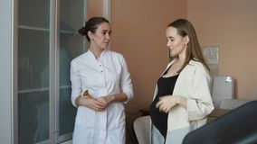 A female doctor and a young pregnant woman are standing in the office and talking about motherhood. A female doctor and a young pregnant woman are standing in stock footage