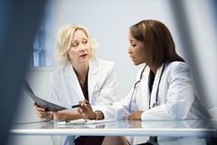 Female doctors. Discussing patient x ray films Royalty Free Stock Image