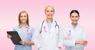 Female doctors with breast cancer awareness ribbon. Healthcare, charity, support and medicine concept - group of female doctors with pink breast cancer awareness Royalty Free Stock Photos