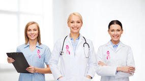 Female doctors with breast cancer awareness ribbon. Healthcare and medicine concept - female doctors with pink breast cancer awareness ribbon Stock Images