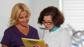 Female doctors examining medical survey documents at the clinic stock photography
