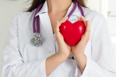 Female doctors's hands holding red heart. In front of her chest. Doctor's hand closeup. Medical help, prophylaxis or insurance concept royalty free stock images