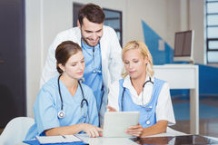 Female doctors using digital tablet while discussing with colleague Stock Image