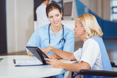 Female doctors using digital tablet while discussing Royalty Free Stock Images