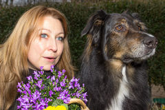 Female and dog looking curious. Female holding a flower basket looking curious with her dog Stock Photo