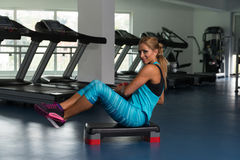 Female Doing Abdominal Exercise With Ball On Stepper. Mature Woman Athlete Doing Abs Exercise With Ball On Stepper As Part Of Bodybuilding Training Royalty Free Stock Image