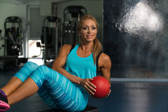Female Doing Abdominal Exercise With Ball On Stepper. Mature Woman Athlete Doing Abs Exercise With Ball On Stepper As Part Of Bodybuilding Training Royalty Free Stock Photos