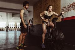 Female doing cardio workout at gym with trainer. Fitness female using air bike for cardio workout at gym with personal trainer. Woman doing intense workout on Stock Image