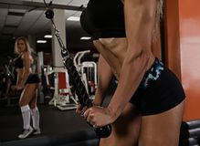 Female doing exercise on triceps. With pulldown station Stock Image