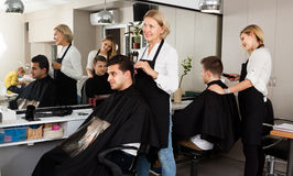Female doing hairstyle for adult man blonde hairdresser serving Stock Photo
