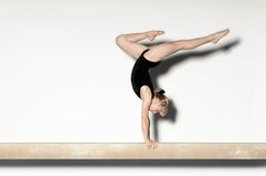Female Doing Handstand On Balance Beam. Side view of a young female doing a handstand on balance beam Royalty Free Stock Image