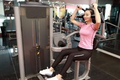 In fitness center woman working. Slim girl sitting and hard working on sport equipment , Female doing push ups in gym. Female doing push ups exercise in gym stock images