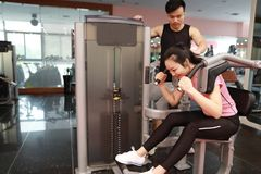 In fitness center woman working. Slim girl sitting and hard working on sport equipment , Female doing push ups in gym. Female doing push ups exercise in gym With royalty free stock images