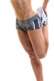 Female doing a quad stretch. Image of a slim female doing a quad stretch royalty free stock images