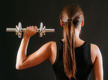 Female doing shoulder press with dumbbell. Photo of the back of a young woman doing a shoulder press with a dumbbell over a dark background royalty free stock photography