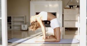 Female Doing Yoga In Her Living Room Stock Photo