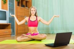 Female doing yoga with laptop Royalty Free Stock Image