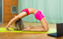 Female doing yoga with laptop Royalty Free Stock Photo