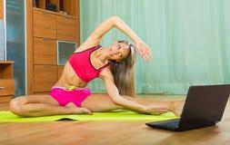 Female doing yoga with laptop Stock Image