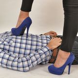 Female Domination. A young woman wearing elegant pumps, dominating in an authoritative manner a man lying down submissively royalty free stock images
