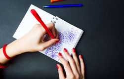 Female drawing flower shapes in notebook Royalty Free Stock Photos