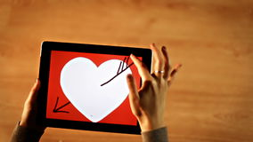 Female drawing heart with arrow on tablet stock video footage