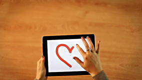 Female drawing heart and heart insight on tablet stock footage