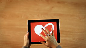 Female drawing  white heart with red background on tablet stock footage