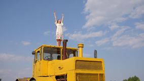 Female in dress raises hands up standing on agricultural machine on background blue sky and white clouds. In slow motion stock footage